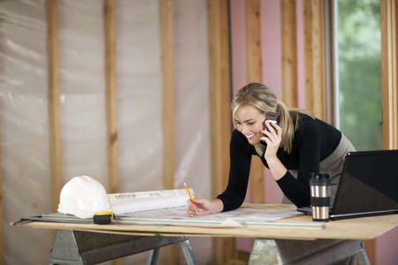 A young woman is looking at blueprints and talking on the phone.  She is working at a construction site.  Horizontally framed shot. Stock Photo