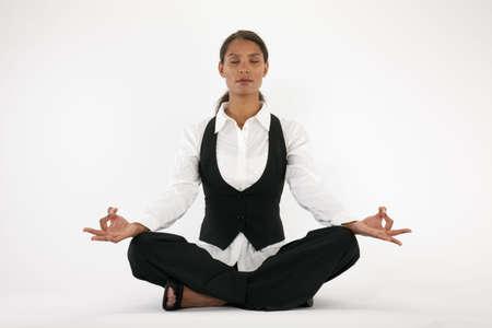 Young woman sitting cross legged and meditating. Horizontally framed shot. Imagens