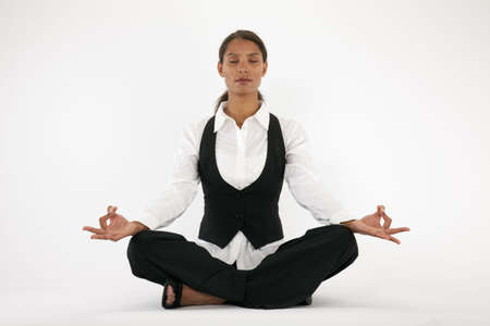 Young woman sitting cross legged and meditating. Horizontally framed shot. Stock Photo
