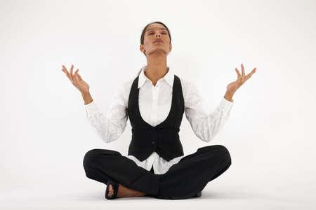 Young woman sitting cross legged and meditating. Horizontally framed shot. Stock Photo