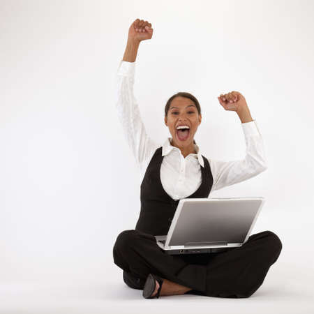 cheering: Young woman sitting on floor using laptop. Square format. Stock Photo