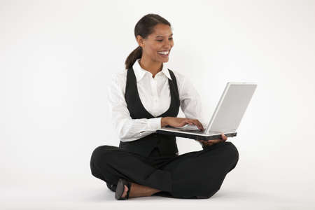 Young woman sitting on floor using laptop. Horizontally format.