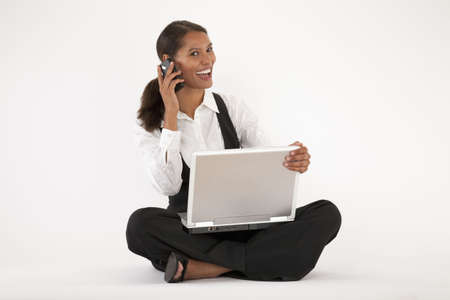 Young woman sitting on floor using laptop and cell phone. Horizontally format. photo