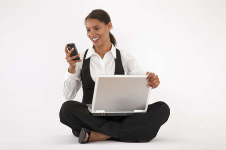 Young woman sitting on floor using laptop and cell phone. Horizontally format.