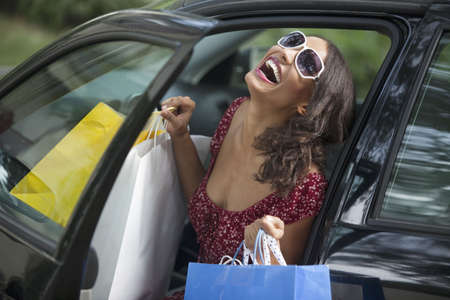 Young woman getting out of car holding shopping bags. Horizontally framed shot. Stock Photo