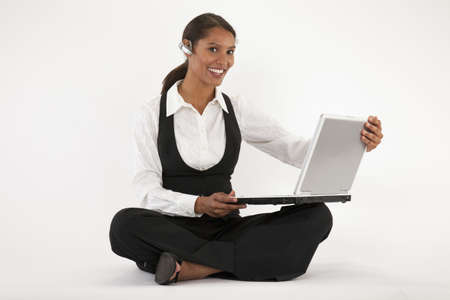 Young woman sitting on floor using laptop and wearing blue tooth headset. Horizontally format.
