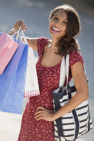 Young woman with shopping bags. Vertically framed shot.