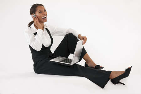Young woman sitting on floor using laptop and wearing bluetooth headset. Horizontally format.