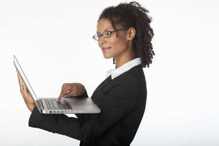 Young businesswoman in profile using laptop. Horizontally framed shot. photo