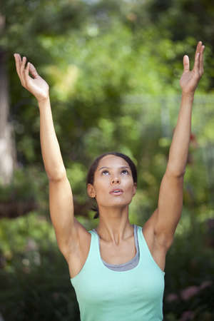 Young woman with arms raised in outdoor setting. Vertically framed shot.