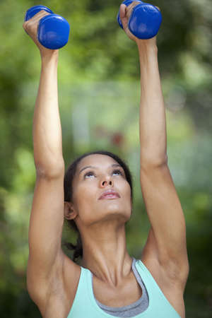 Young woman exercising in outdoor setting. Vertically framed shot. photo
