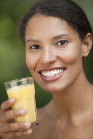 Closeup of young woman drinking orange juice in outdoor setting. Vertically framed shot.