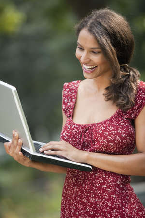 Young woman using laptop in outdoor setting. Vertically framed shot. photo