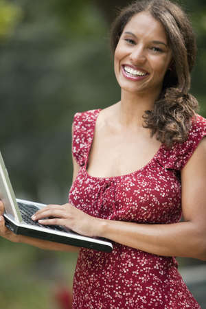Young woman using laptop in outdoor setting. Vertically framed shot.