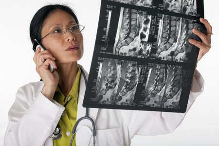 midlife: Asian female doctor looking at an MRI scan while talking on a cellphone. Horizontal shot. Isolated on white. Stock Photo