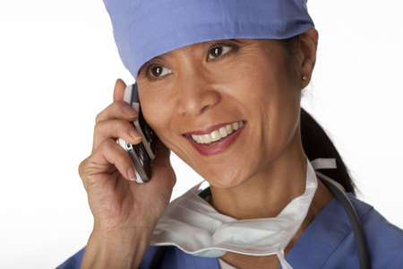 Closeup, cropped view of an Asian female medical professional wearing scrubs and talking on a cell phone. Horizontal shot. Isolated on white. photo