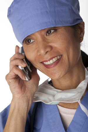 Closeup, cropped view of an Asian female medical professional wearing scrubs and talking on a cell phone. Vertical shot. Isolated on white.