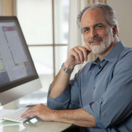 Portrait of a businessman dressed in casual clothing and sitting in front of a computer. He is smiling at the camera with one hand on the keyboard and the other near his face. Square format. Stock Photo - 6593459