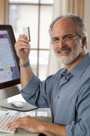 A businessman sitting in front of a computer monitor and holding up a credit card.  He is smiling at the camera. Vertical shot. Stock Photo
