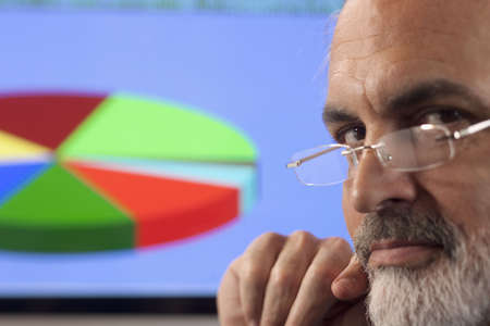 Close-up portrait of a businessman looking pensively at the camera. A computer monitor displaying a multi-colored pie chart can be seen in the background. Horizontal shot. photo