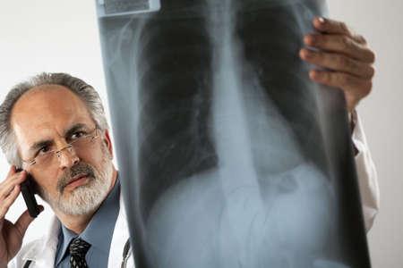lab coat: Immagine di fuoco di un medico che indossa occhiali e un laboratorio bianco cappotto e guardando intensamente una radiografia mentre usando il suo telefono cellulare. Tiro orizzontale.  Archivio Fotografico