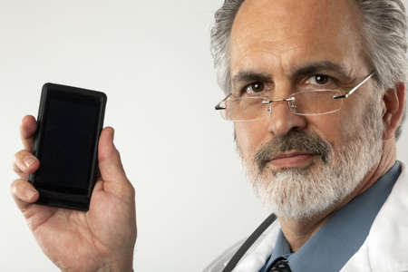Portrait of a doctor wearing glasses and a white lab coat.  He is holding up a cell phone and looking at the camera. Horizontal shot.