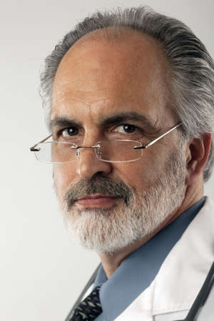 Close-up portrait of a doctor wearing glasses and a white lab coat.  He is looking at the camera with a serious expression. Vertical format. photo