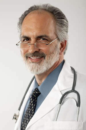 Portrait of a doctor wearing glasses and a white lab coat, with a stethoscope draped around his neck.  He is looking at the camera and smiling. Vertical format.
