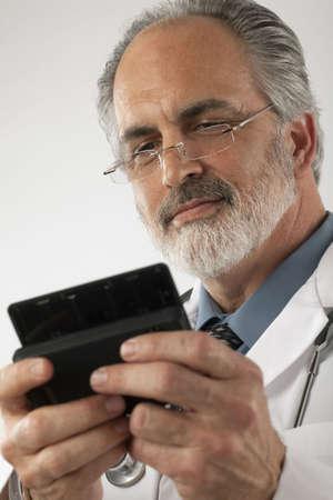 lab coat: Primo piano di un medico che indossa occhiali e un laboratorio cappotto e texting su un telefono cellulare. Girato verticale.