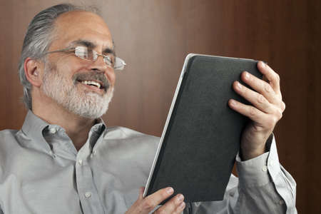 Portrait of a smiling businessman reading information from an electronic tablet. Horizontal shot. Stock Photo