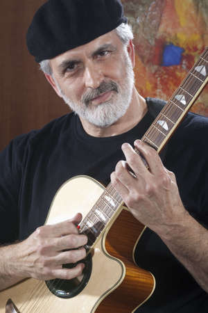 Portrait of a middle-aged man wearing a black beret and t-shirt and playing an acoustic guitar. He is looking at the camera. Vertical shot.