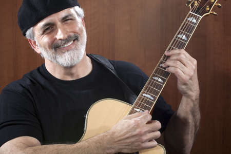 Portrait of a middle-aged man wearing a black beret and t-shirt and playing an acoustic guitar. He is smiling at the camera. Horizontal shot. Stock Photo
