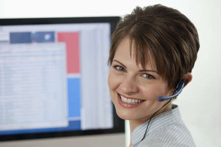 An attractive young businesswoman is wearing a headset and smiling at the camera with a computer monitor in the background. Horizontal shot.