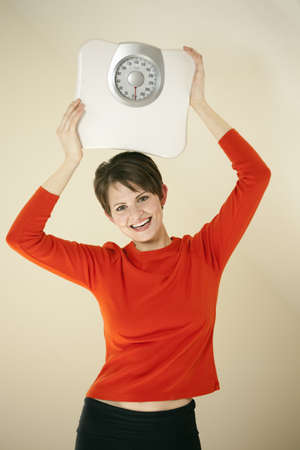 Attractive young woman holds a bathroom scale above her head while smiling at the camera. Vertical shot.
