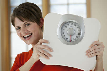 Attractive young woman holds a bathroom scale up while smiling at the camera. Horizontal shot.