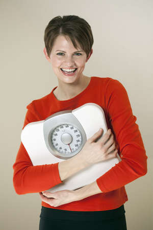 Attractive young woman holds a bathroom scale to her chest while smiling at the camera. Vertical shot.