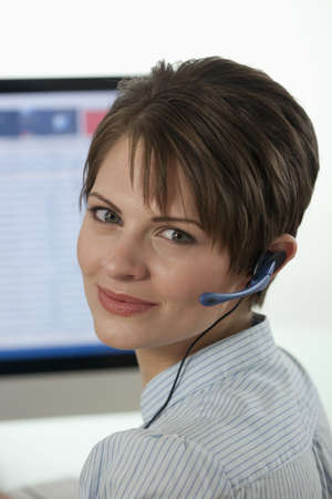 An attractive young businesswoman is wearing a headset and smiling at the camera with a computer monitor in the background. Vertical shot.