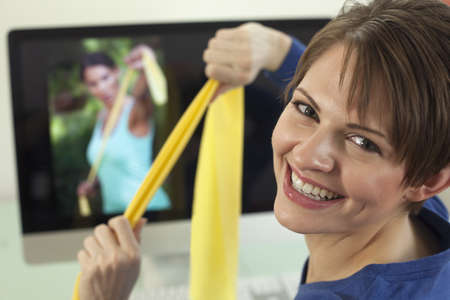 Attractive young woman pulls on resistance bands while smiling back at the camera. An exercise video is playing in the background. Horizontal shot.