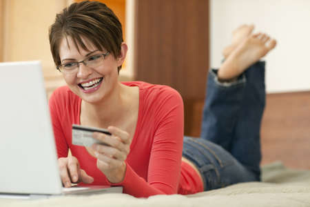 Attractive young woman holds up the credit card she is using to shop with on her laptop computer. Horizontal shot. Stock Photo