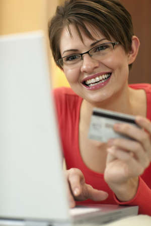 Attractive young woman holds up the credit card she is using to shop with on her laptop computer. Vertical shot. Stock Photo
