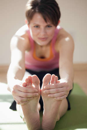 Attractive young woman sits on the floor and stretches to touch her toes. Vertical shot.