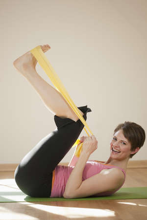 Attractive young woman lies on her back and exercises with resistance bands. She is smiling at the camera. Vertical shot. Stock Photo