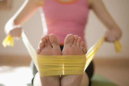 Woman exercises with resistance bands around her feet. Horizontal shot. Stock Photo