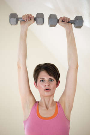 Attractive young woman exercises with dumbbells raised above her head. Vertical shot.