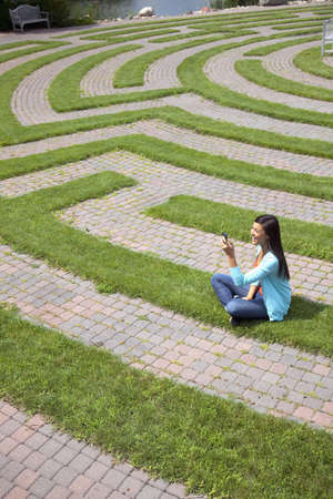 Beautiful young Asian woman laughs at a text message on her cellphone while sitting in a grass labyrinth. Stock Photo