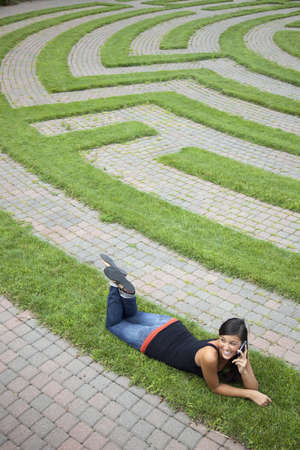 Beautiful young Asian woman lies down on the grass of a park labyrinth while enjoying a conversation on her cellphone. Vertical shot. Stock Photo