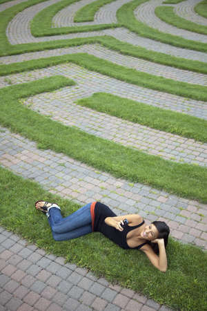 Beautiful young Asian woman smiles as she texts on her cellphone while lying on a grass labyrinth. Vertical shot