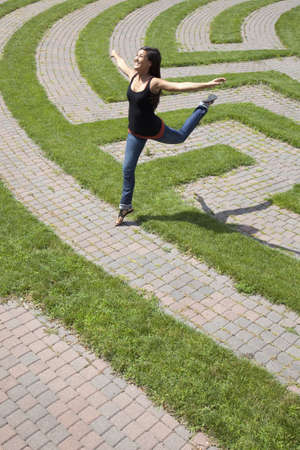 Beautiful young Asian woman playfully jumps over the grass boundary of a park labyrinth. Vertical shot.