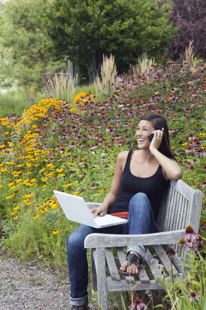 Cute young woman laughs while talking on the phone and working on a laptop. She is seated on a park bench amid blooming flowers and trees. Vertical shot.