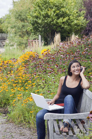 Cute young woman smiles while seated on a park bench with a laptop and mobile phone. Trees and flowers are in the background. Vertical shot. Stock Photo